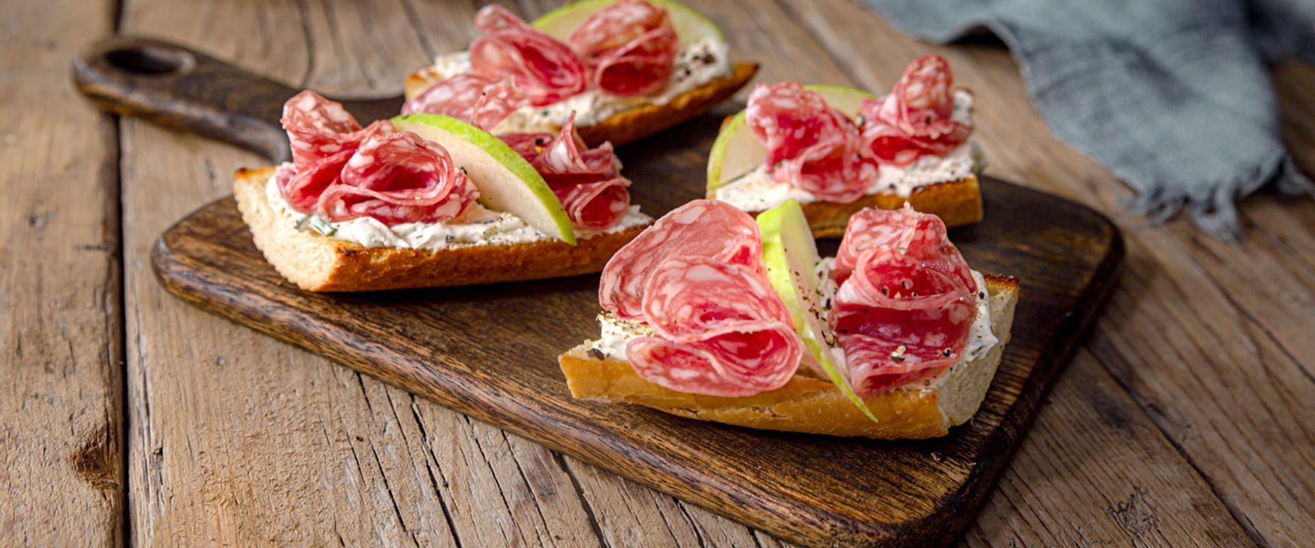 Tagliere di legno con fette di pane condite con salame